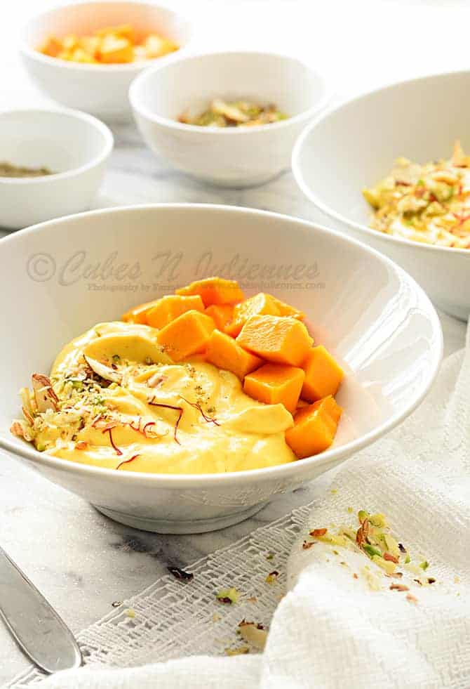 Close up shot of mango shrikhand in white bowl, nuts, cubed mangoes in bowls at the back.