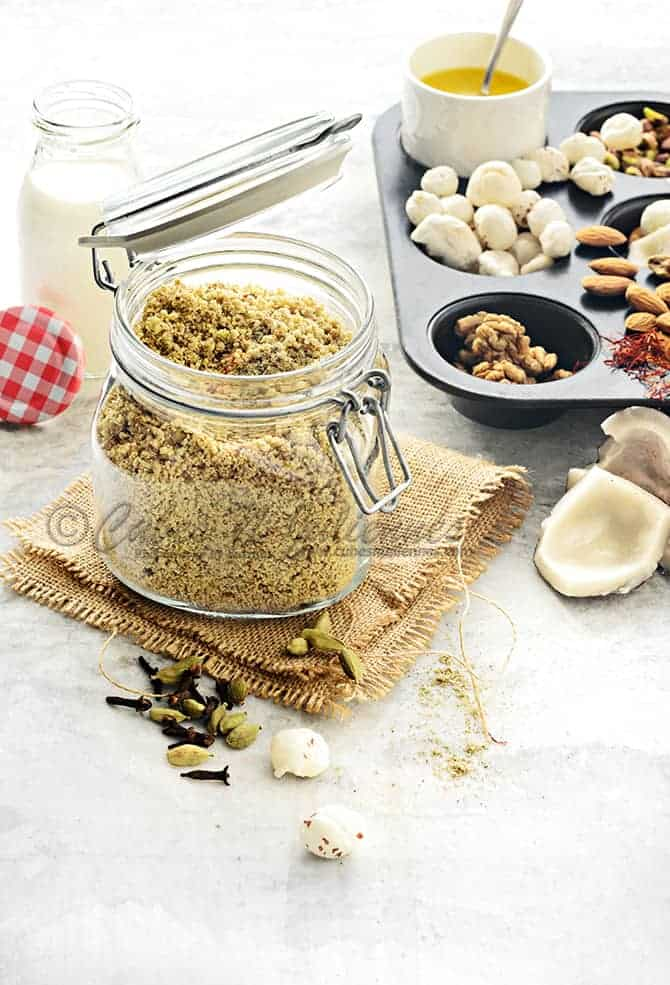 dry fruit and nuts powder in glass jar with milk bottle and nuts at the back