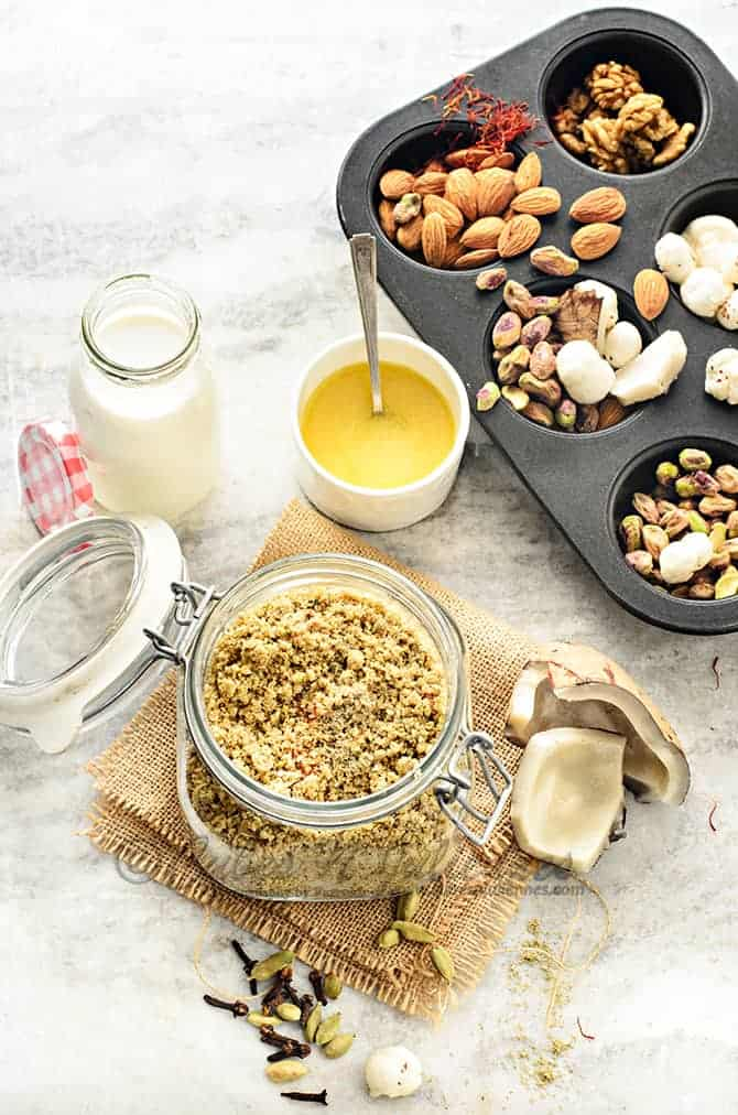 Dry fruits and nuts powder in glass jar with milk, ghee and some nuts on the side