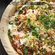 Close up shot of dahi pakodi chaat in brown plate.