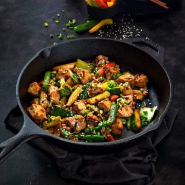 Chicken Stir Fry in a cast iron pan with some bell peppers at the back