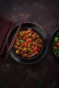 Indo Chinese vegan Mushroom Manchurian served in black bowl with a pair of chopsticks in it.