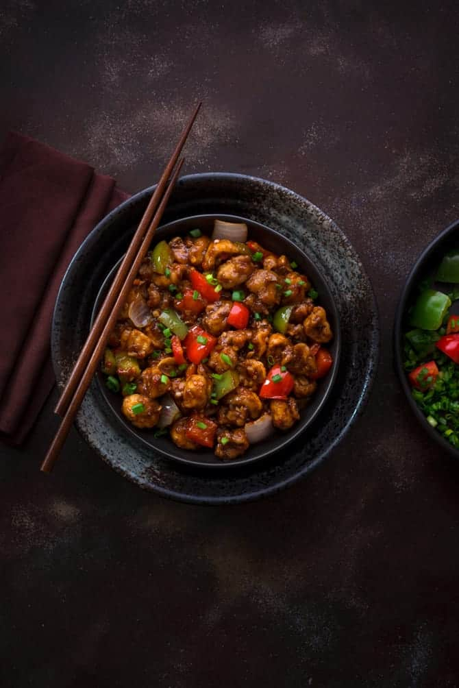 Crispy Vegan Indo Chinese Mushroom Manchurian served in black bowl with pair of chopsticks in it.