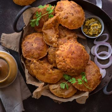 Rajma Masala Puri served on traditional platter with onions and pickle on the side