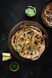 Tawa Garlic Naan on black plate with butter, salad and dal makhani on the side