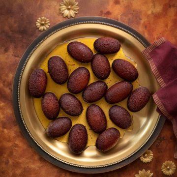 Overhead shot of Milk Powder Gulab Jamun served on traditional brass plate