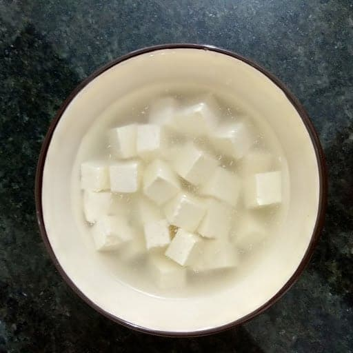 Paneer cubes soaked in hot water in bowl.