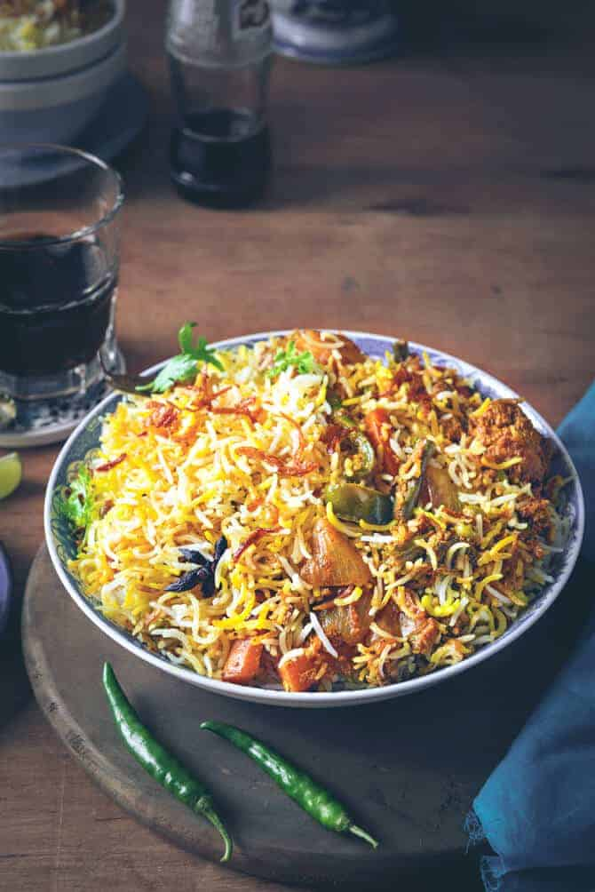 Hyderabadi vegetable Biryani served in blue bowl with soft drink on the side