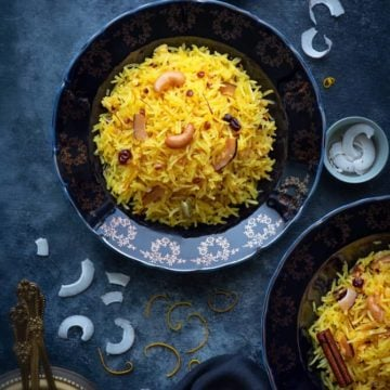 An over head shot of zarda served in served in a two blue plates, coconut slices and orange zest in a small bowl and around