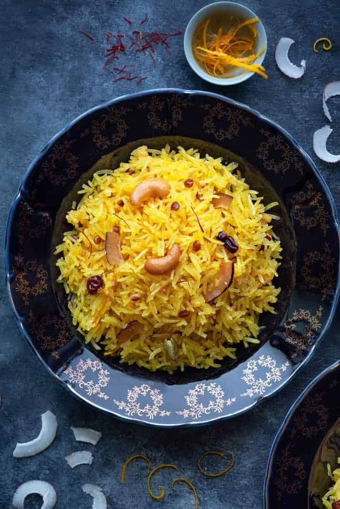 A close-up shot of Zarda pulao (sweet rice) served on a blue plate. Some orange zest, coconut slices spread around