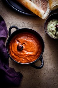 Spicy tangy Onion tomato chutney in a black bowl, dosa and white coconut chutney on the side