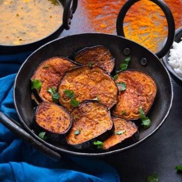 Tawa fried Bengali Begun Bhaja ( baingan fry) in a kadhai (wok)