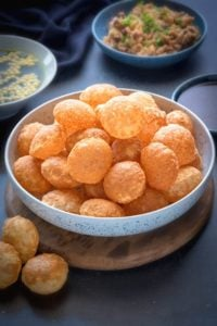 Crisp puffed Golgappa Puri for pani puri in a large bowl. Golgappa pani, its filling and sweet chutney in abowl at the back.