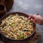 Kid's hand holding a spoon kept in sabudana khichdi which is served in a wooden bowl.