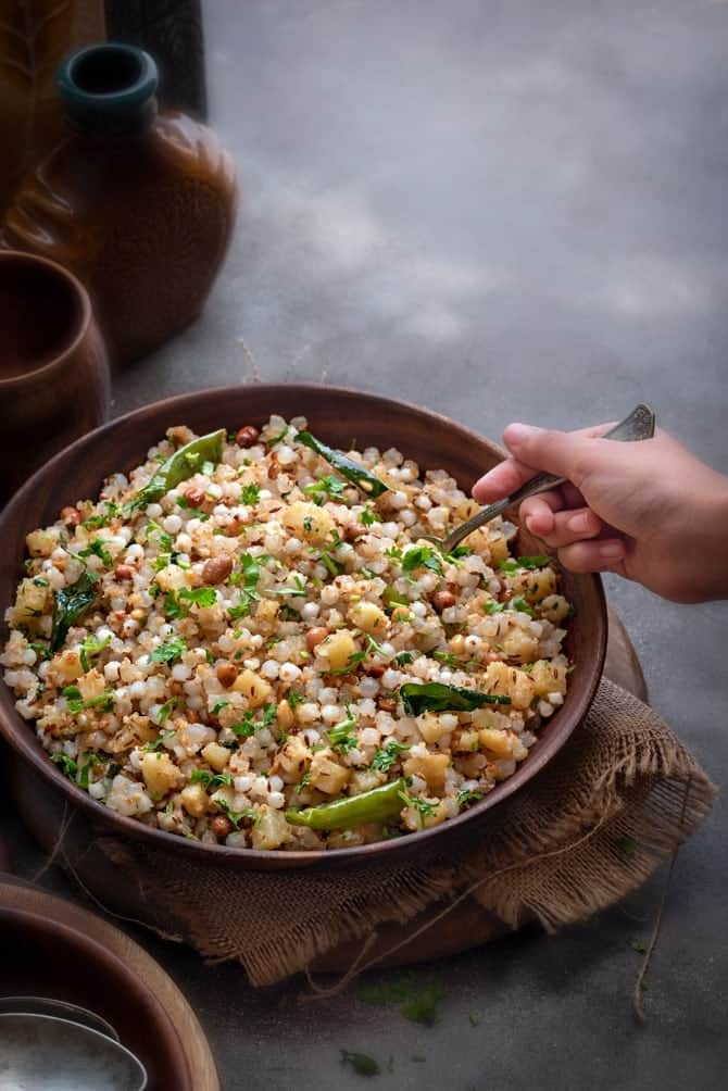 Kid's hand holding a spoon kept in sabudana khichdi which is served in a wooden bowl