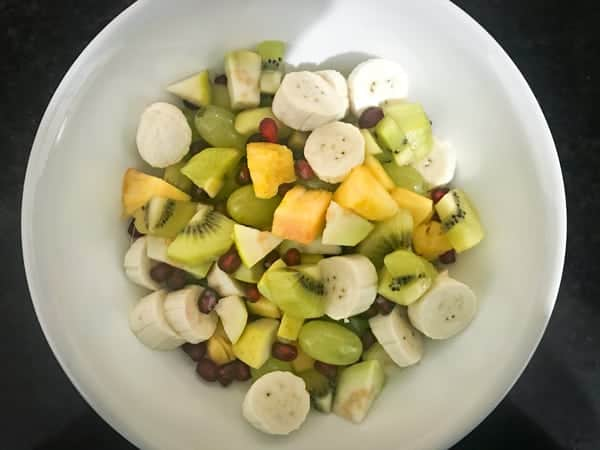 Mixed fruit cubes in a white bowl.
