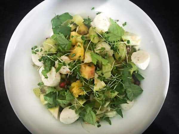 Mixed fruit chaat topped with mint, micro greens, spices and honey in white bowl.