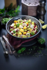 Indian style spiced mixed fruit salad served in a large black bowl. Some microgreens in a small bowl with lemon wedges and fresh mint around.