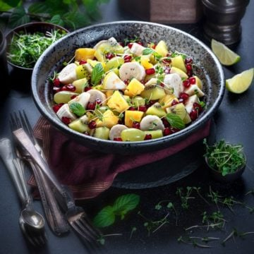Indian style spiced mixed fruit chaat salad served in a large black bowl