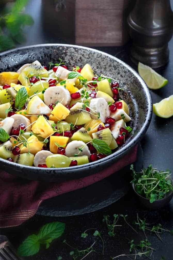 Close up shot of Indian style fruit chaat salad in a large black bowl, lemon wedges on side.
