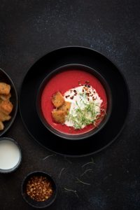 Overhead shot of beetroot tomato soup in lack bowl with croutons on the side