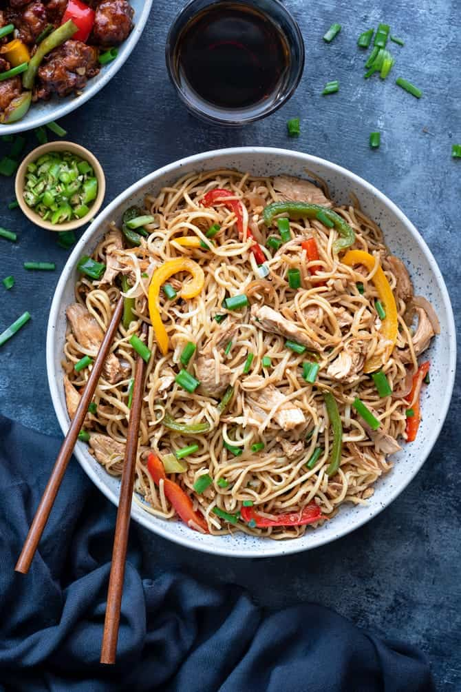 Street style Chinese Chicken Hakka Noodles served in a large bowl, with chopped green chilies and cold drink on the side.
