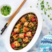 Spicy Chilli Paneer gravy erved in a white oval plate with a pair of chopsticks