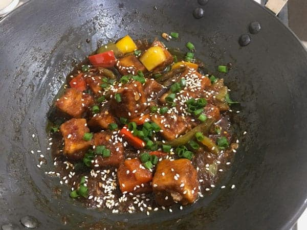 Sesame seeds, spring onions added in a wok to finish the Chilli Paneer dish.