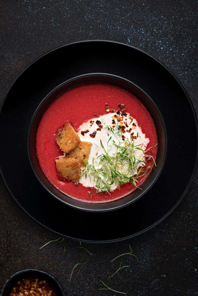 Close-up shot of beetroot tomato soup in black bowl
