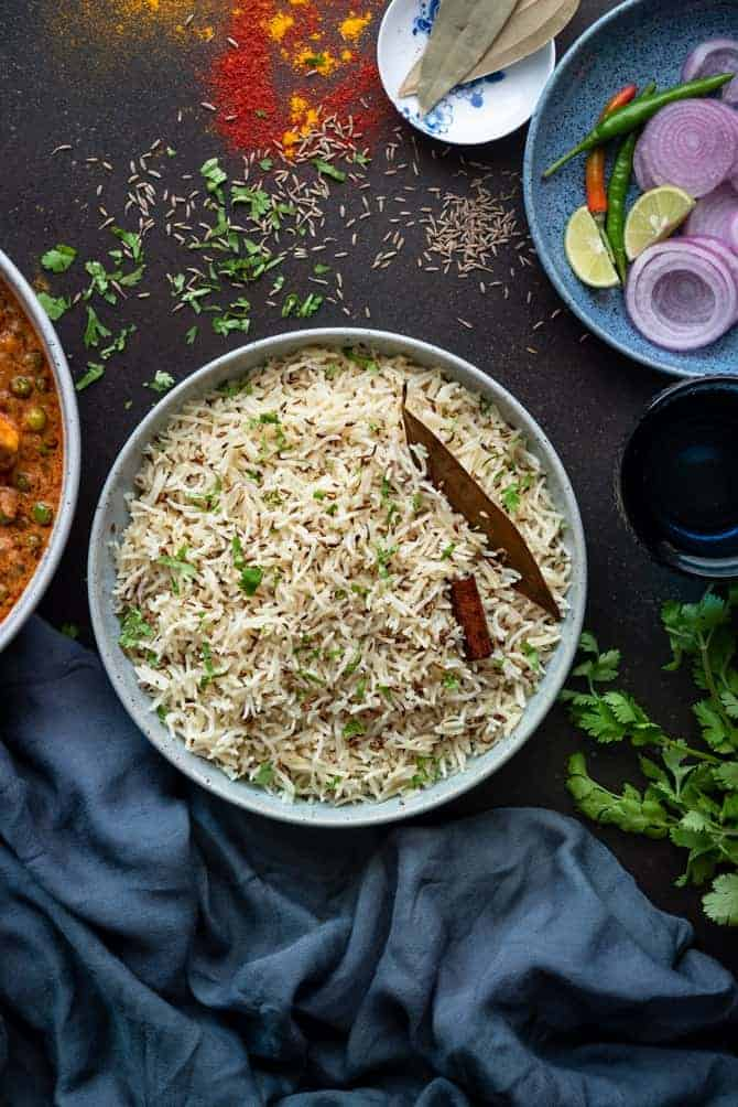 Jeera rice or Zeera rice served in large bowl with salad and curry on the side