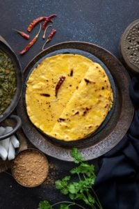 Punjabi Makki Ki Roti topped with ghee and served on a traditional plate with jaggery, radish and saag on the side