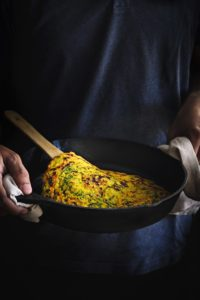 A pair of hands holding an iron pan with moong dal chilla in it.