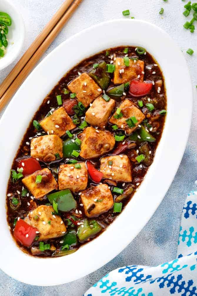 Close-up shot of Indo Chinese Chilli Paneer gravy served in an oval white plate