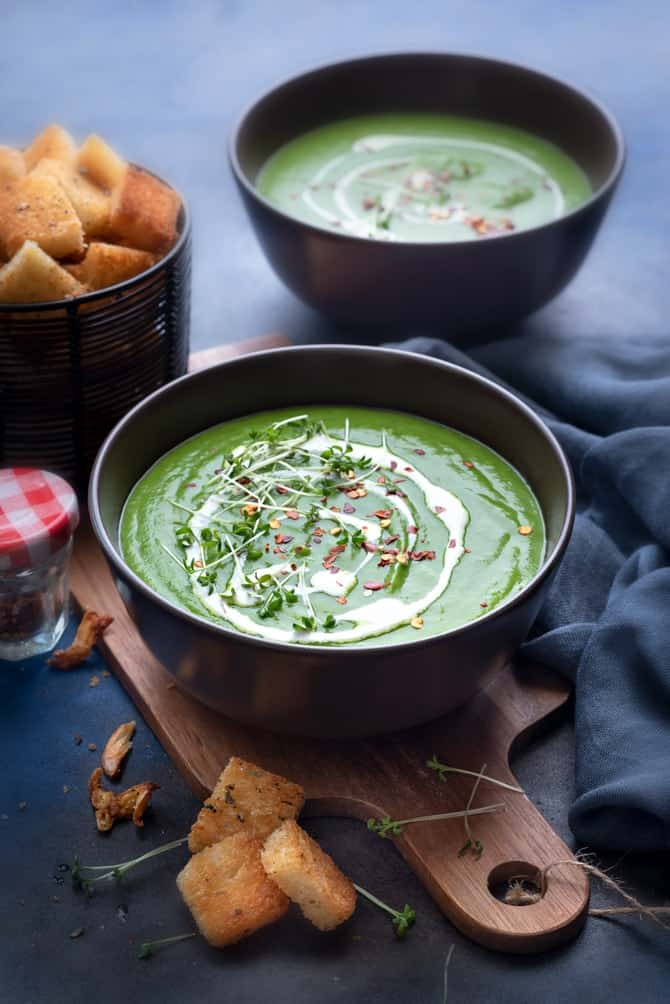 Garnished green pea soup in two brown bowls with croutons on the side