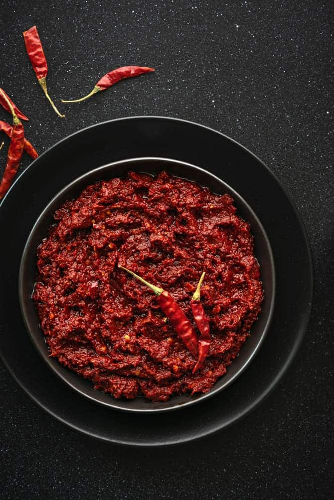 Close-up shot of red chili paste on black plate.