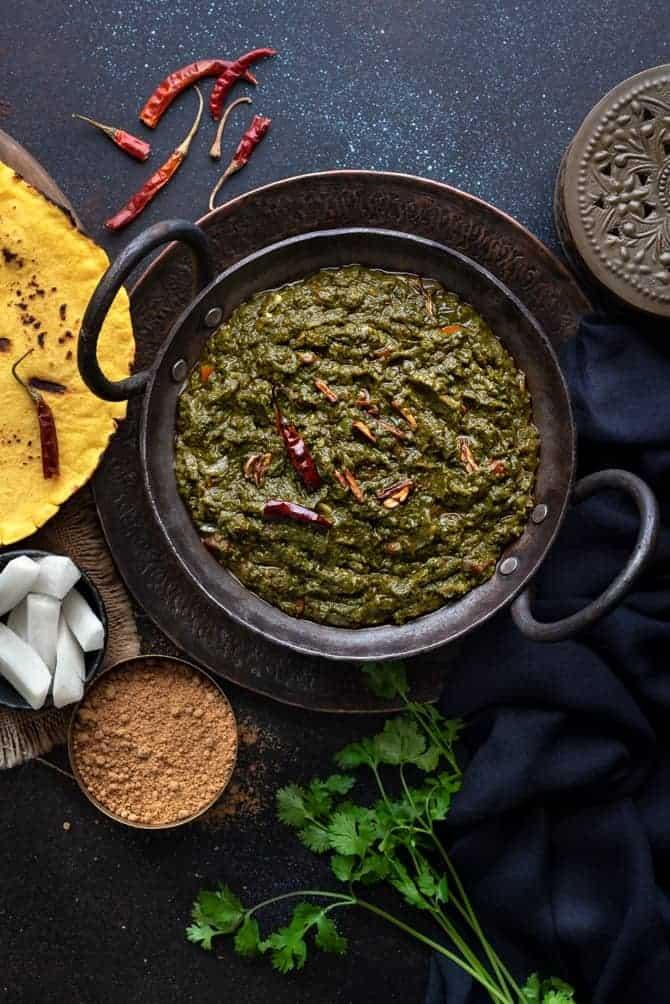 Punjabi Sarson ka Saag served in a kadhai (wok) with makki ki roti, radish and jaggery on the side