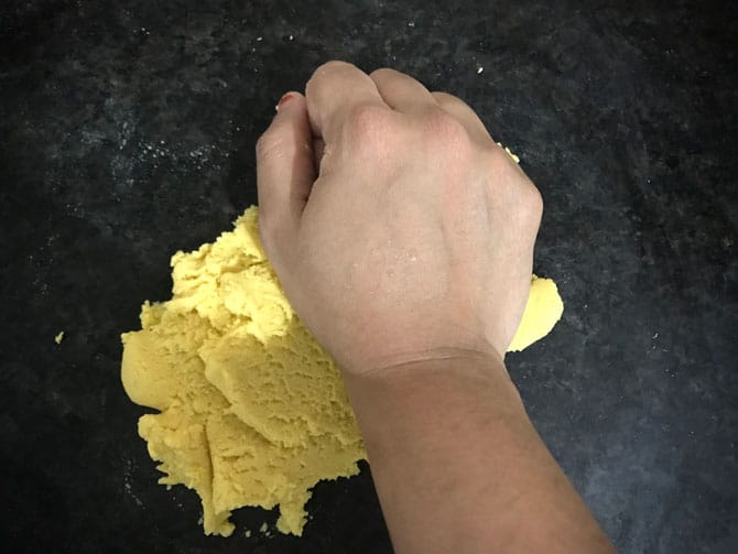 Kneading the dough ball with the heels of the palm, just before shaping them