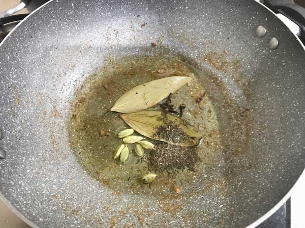 Bay leaves, green cardamom, cloves and shajeera added in hot oil in pan