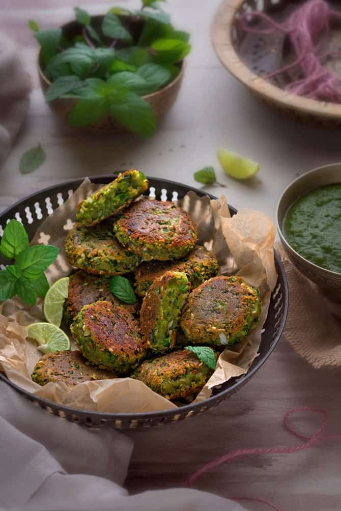 Crisp Paneer Matar Kabab served in a traditional brass bowl with green chutney on the side.