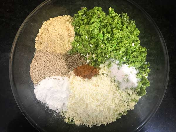Paneer, coarse peas mixture, seeds, spice powders, salt, and flours added in a bowl