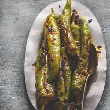 Bharwa mirchi fry served on oval metal plate.