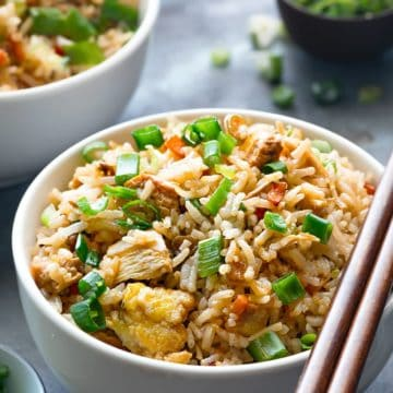 Close up shot of best chicken fried rice in white bowl with a pair of chopsticks