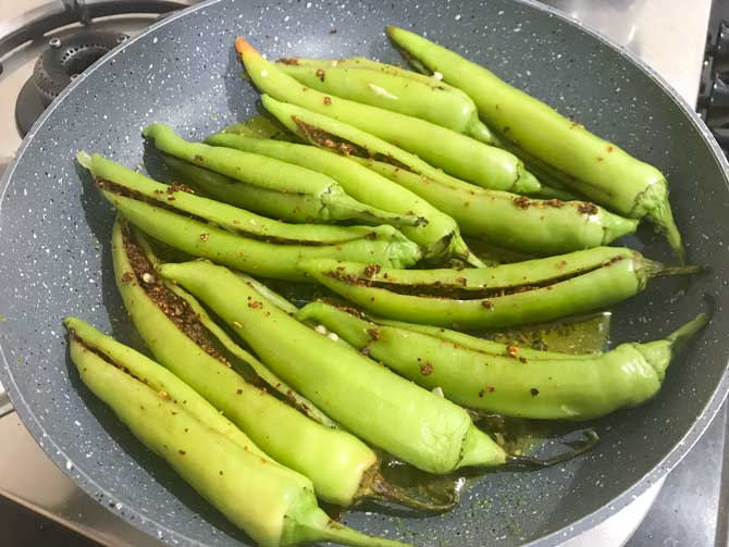 Bharwa mirchi or stuffed green chillies added in pan