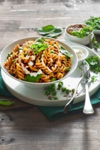 Fusilli Pasta with spinach and tomatoes served in white bowl with some cream on the side