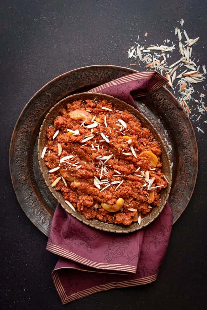 Gajar Ka halwa or carrot with milkmaid in traditional oval brass platter with almonds spread around
