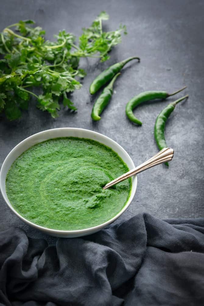 Spicy Green Chutney in small bowl with coriander and chilli at the back