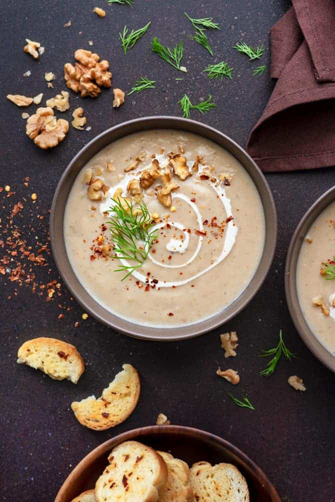 Creamy Cauliflower soup served in two brown ceramic bowls with croutons on the side