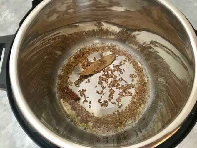 Cumin seeds, cinnamon, cardamom, bay leaf added in the hot oil in Instant pot