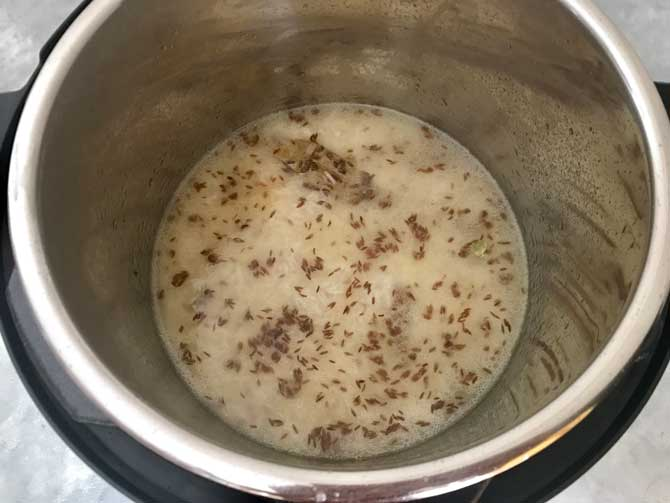 Strained rice, salt and water added in instant pot to make jeera rice