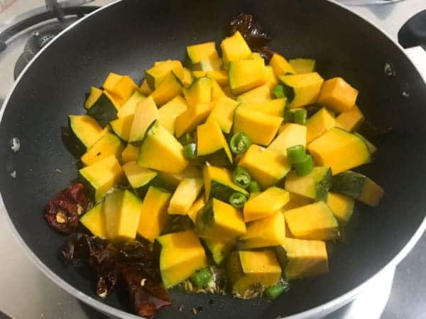 Cubed pumpkin and green chilies added in pan